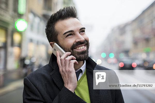 Lächelnder Geschäftsmann in der Stadt am Handy