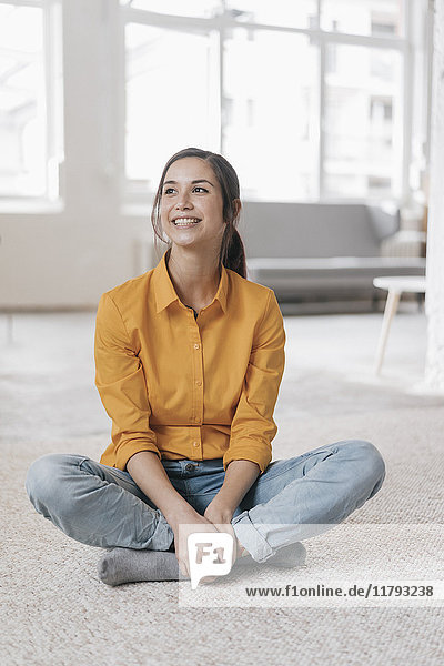 Young woman sitting on floor  smiling