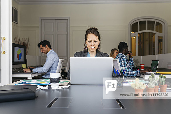 Young businesswoman using laptop  colleagues working in background