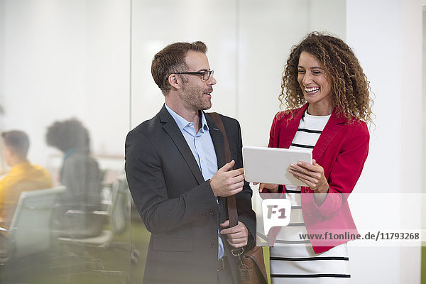 Geschäftsmann und Geschäftsfrau mit Tablettengespräch im Büro