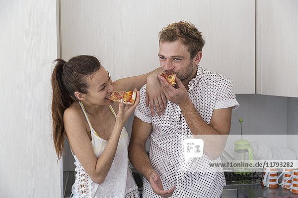 Glückliches junges Paar beim Pizzaessen in der Küche