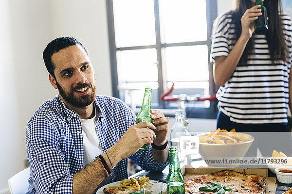 Mann und Frau mit Bierflaschen am Esstisch
