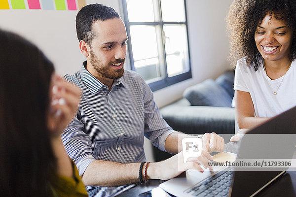 Lächelnde Geschäftsleute teilen Laptop im Büro