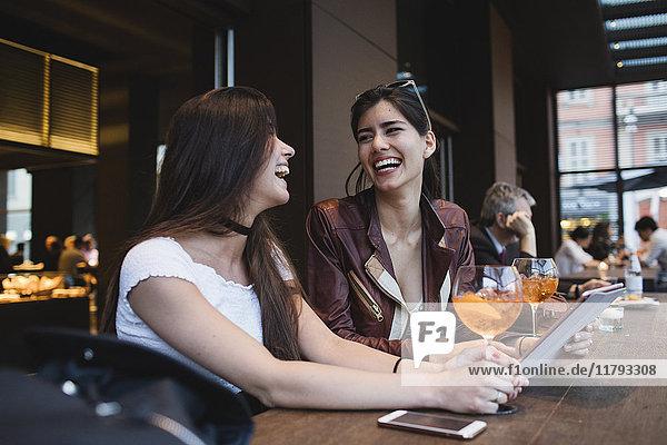 Zwei glückliche junge Frauen in einer Bar