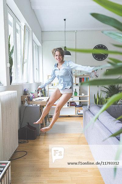 Aufgeregte junge Frau beim Springen zu Hause