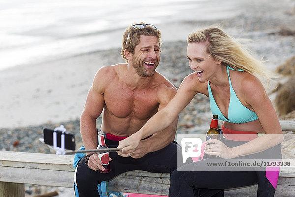 Ein Paar hat Spaß am Strand und nimmt sich einen Selfie.