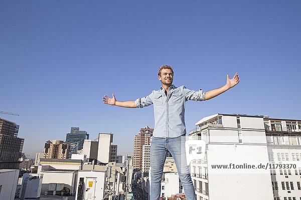 Junger Mann steht auf der Dachterrasse mit ausgestreckten Armen