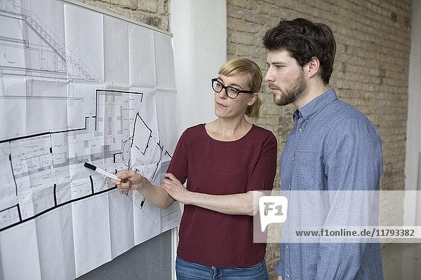 Geschäftsfrau erklärt jungen Kollegen neues Projekt