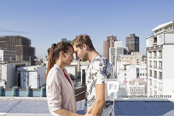 Junges Paar beim Flirten auf einer Dachterrasse