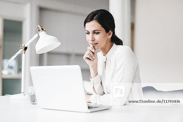 Geschäftsfrau mit Laptop am Tisch denkend