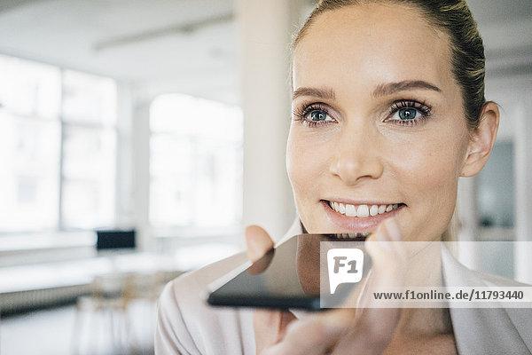 Portrait einer lächelnden Geschäftsfrau mit dem Handy