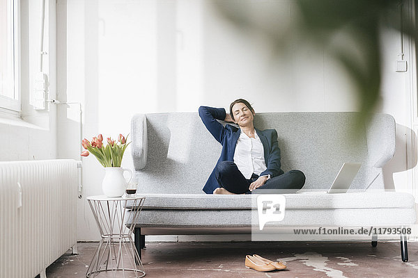 Geschäftsfrau entspannt auf der Couch im Loft