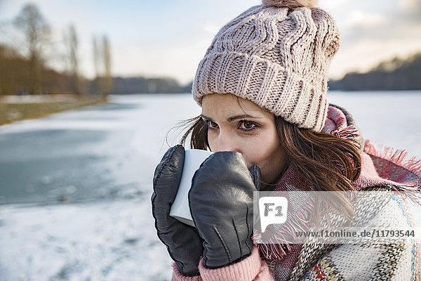Frau trinkt im Winter ein heißes Getränk aus einer Tasse im Freien.