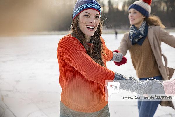 Weibliche Freunde Schlittschuhlaufen im Kreis auf dem zugefrorenen See