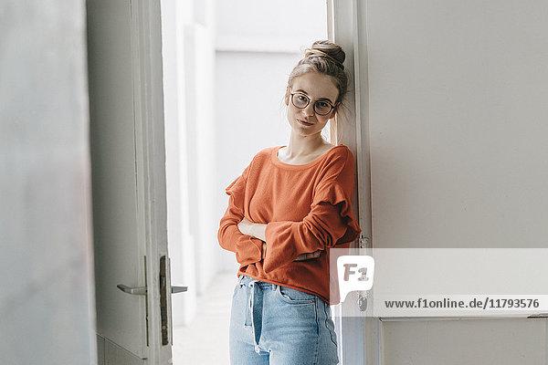 Porträt einer jungen Frau  die sich gegen die Tür lehnt.