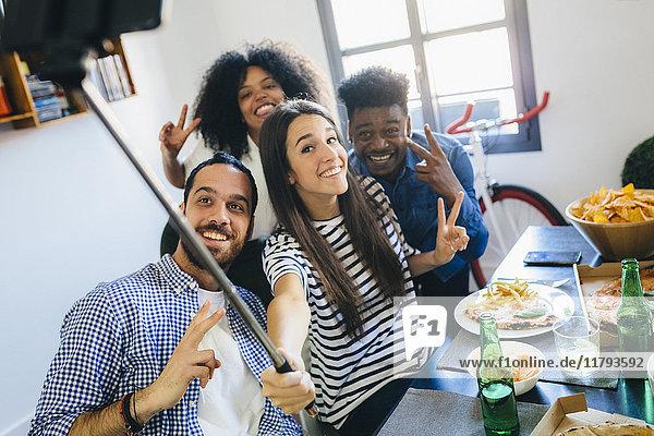 Gruppe von Freunden  die für einen Selfie am Esstisch zu Hause posieren.