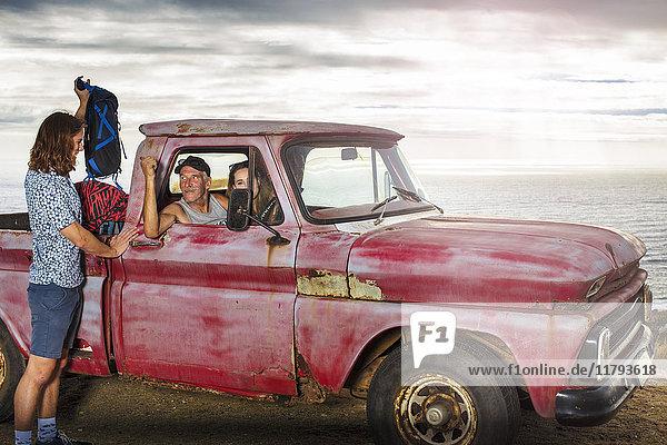 Junger Mann  der seine Sachen von einem alten Pick-Up an der Küste mitnimmt.