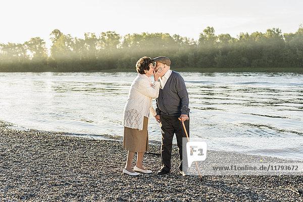 Glückliches Seniorenpaar beim Küssen am Strand