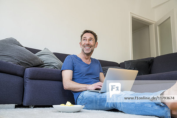 Porträt eines lachenden Mannes mit Laptop auf dem Boden im Wohnzimmer sitzend