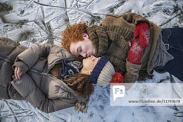 Paar auf gefrorener Seeoberfläche liegend küssend