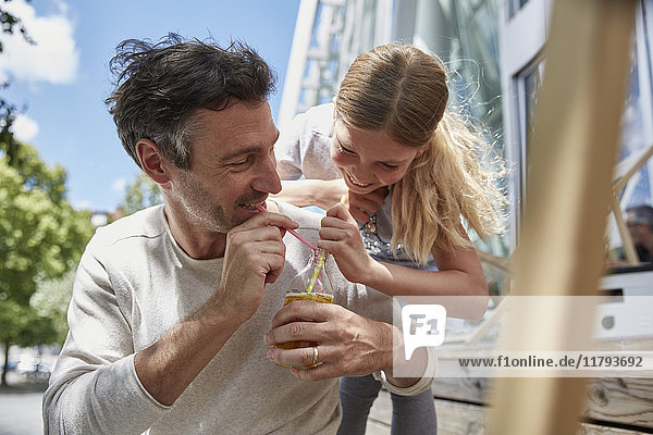Father and daughter sharing drink at an outdoor cafe