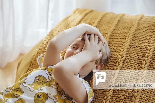 Kleiner Junge  der mit den Händen auf dem Kissen liegt.