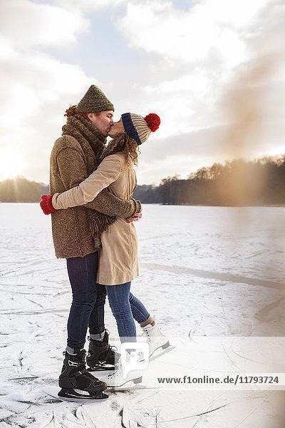 Paar mit Schlittschuhen küssend auf gefrorenem See