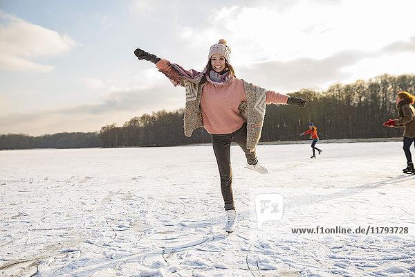 Frau tanzt mit Freunden mit Schlittschuhen auf dem zugefrorenen See