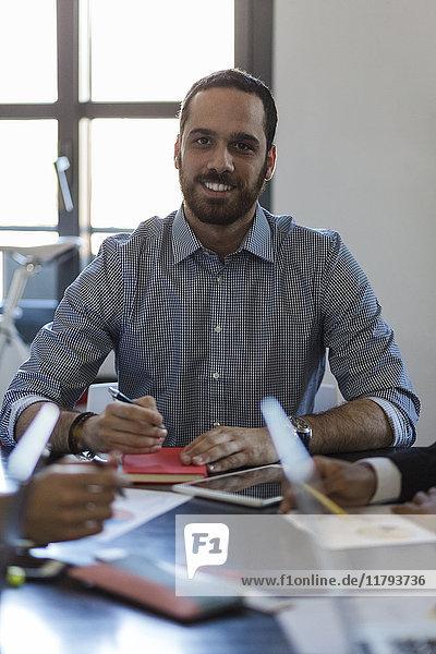 Porträt eines lächelnden Geschäftsmannes bei einer Besprechung im Büro
