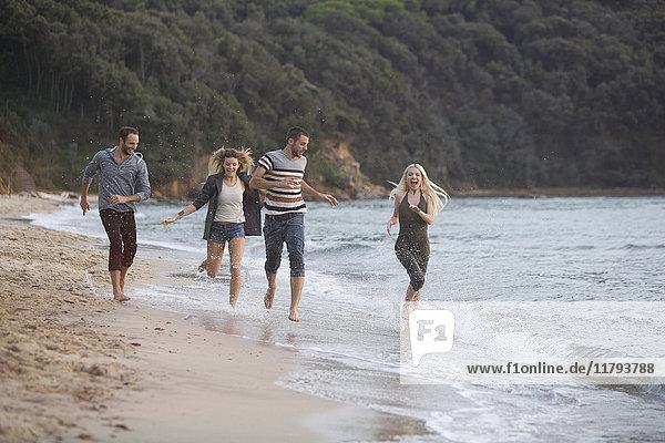 Vier glückliche Freunde beim Laufen am Strand