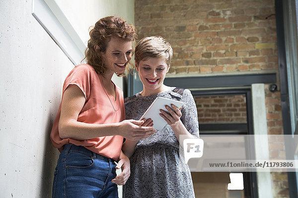 Zwei lächelnde Kollegen teilen sich die Tablette