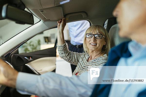 Seniorenpaar probiert Auto im Autohaus aus