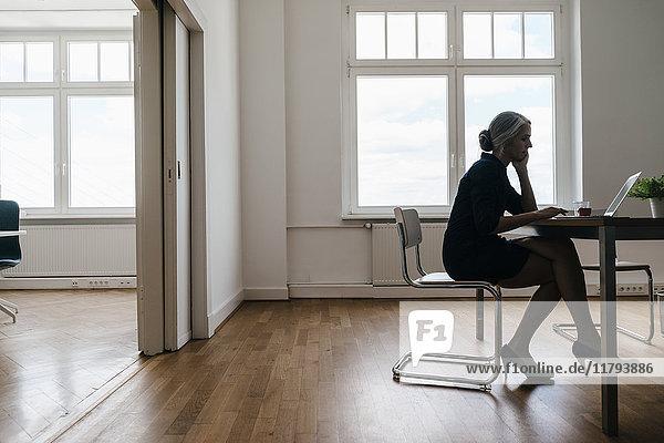 Geschäftsfrau bei der Arbeit am Laptop im Büro