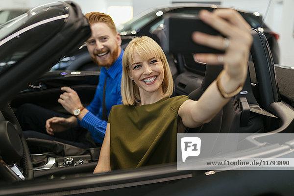 Paar  das sich selbst nimmt  sitzt im Cabrio im Autohaus