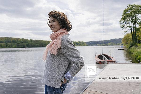 Frau am See stehend mit Blick auf den See