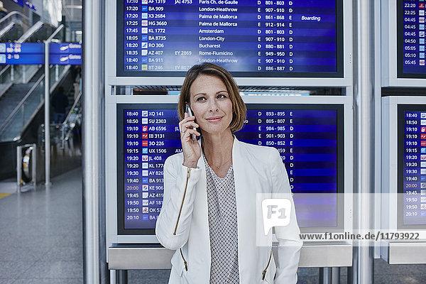 Geschäftsfrau mit Handy im Flugplan am Flughafen