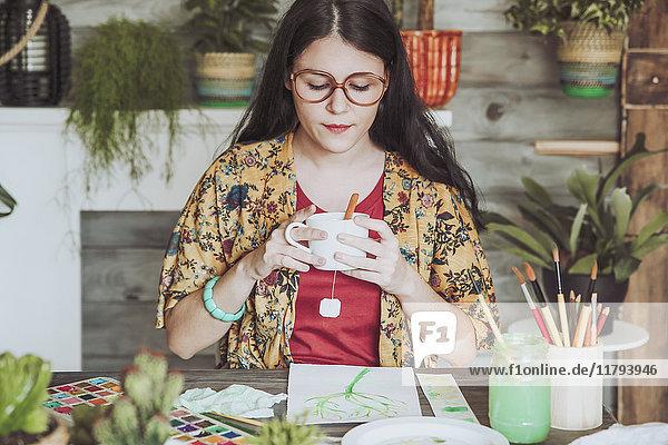 Junge Woan trinkt Tee und schaut sich ihre Pflanzenbilder an.