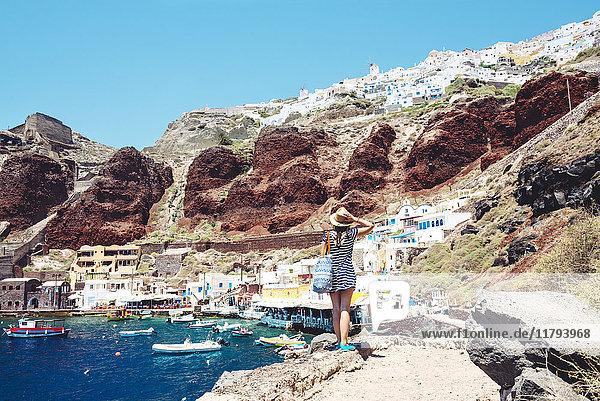 Griechenland  Santorini  Oia  Frau genießt die Aussicht im Fischerhafen mit dem weißen Dorf über der Klippe