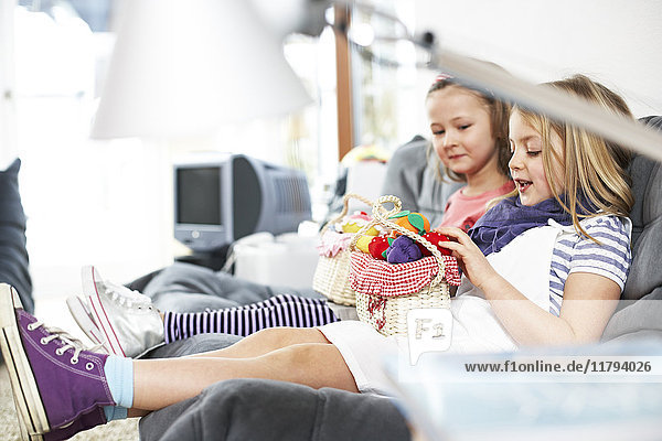Two little girls sitting side by side on the couch