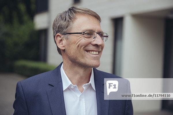 Porträt eines lächelnden reifen Geschäftsmannes im Freien