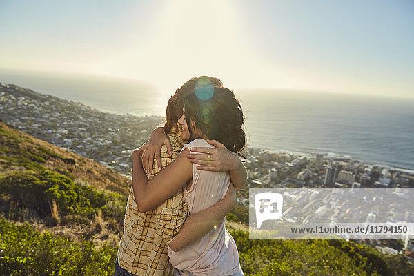 Südafrika  Kapstadt  Signal Hill  zwei junge Frauen  die sich über der Stadt umarmen