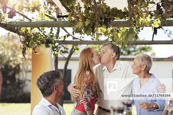 Fröhliches Seniorenpaar mit Familie beim gemeinsamen Mittagessen im Freien