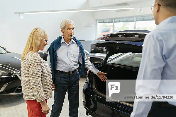 Seniorenpaar im Gespräch mit Verkäufer im Autohaus