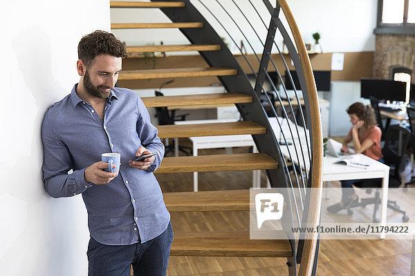 Lächelnder Mann im modernen Büro mit Blick auf das Handy