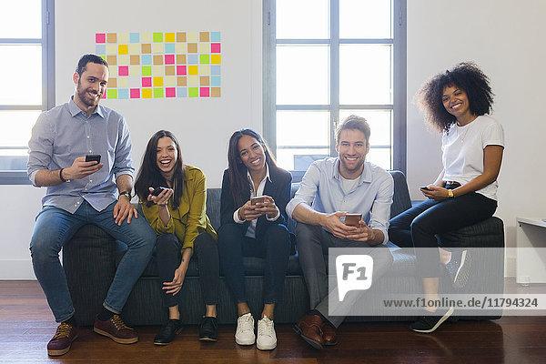 Porträt von glücklichen Kollegen auf der Couch mit Mobiltelefonen