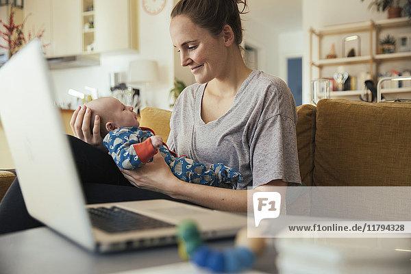 Mutter hält ihr neugeborenes Baby zu Hause neben dem Laptop