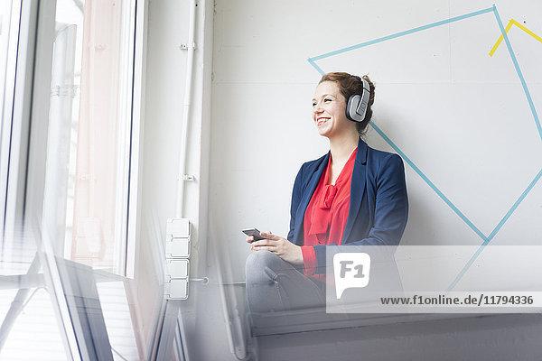 Businesswoman making a call  wearing headphones