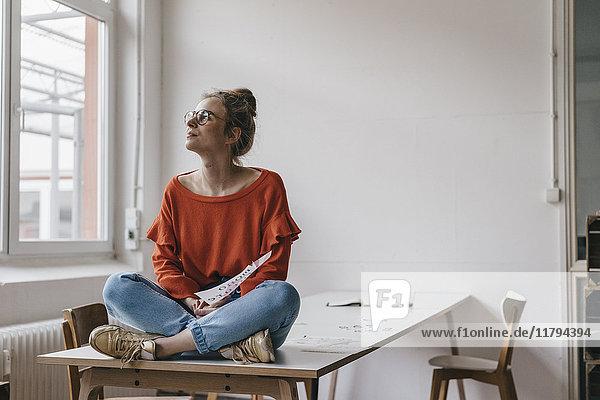 Junge Frau sitzt auf dem Tisch und denkt.