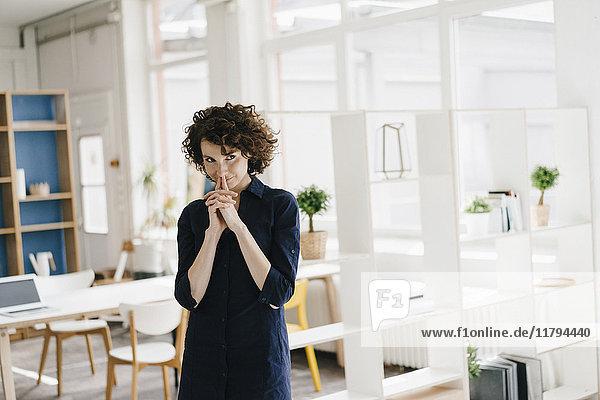 Geschäftsfrau im Büro denken und lächeln