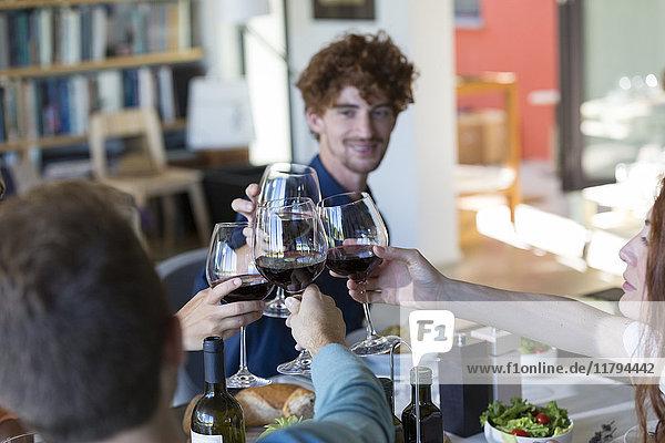 Freunde toasten mit Rotwein